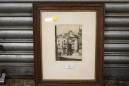 A FRAMED AND GLAZED SIGNED ETCHING DEPICTING A TOWN SCENE