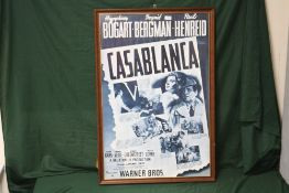 A LARGE REPRODUCTION FRAMED AND GLAZED ADVERTISING POSTER FOR WARNER BROS. 'CASABLANCA' OVERALL SIZE