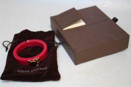LOUIS VUITTON - A RESIN 'LOCK ME' HINGED BANGLE, with original box and Louis Vuitton drawstring bag