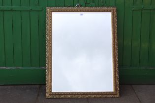 A LARGE GILT FRAMED BEVEL EDGE WALL MIRROR, OVERALL SIZE INCLUDING FRAME 89 X 105 CM