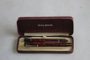 A CONWAY STEWART BOXED SET, A UNIVERSAL 479 FOUNTAIN PEN AND MATCHING PENCIL, in red marble finish