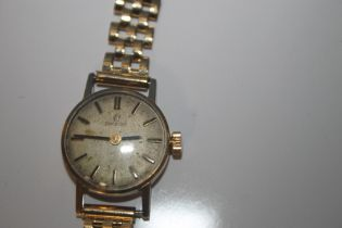 A LADIES OMEGA MANUAL WIND WRIST WATCH on an unbranded 9 ct gold strap, dedication inscription to