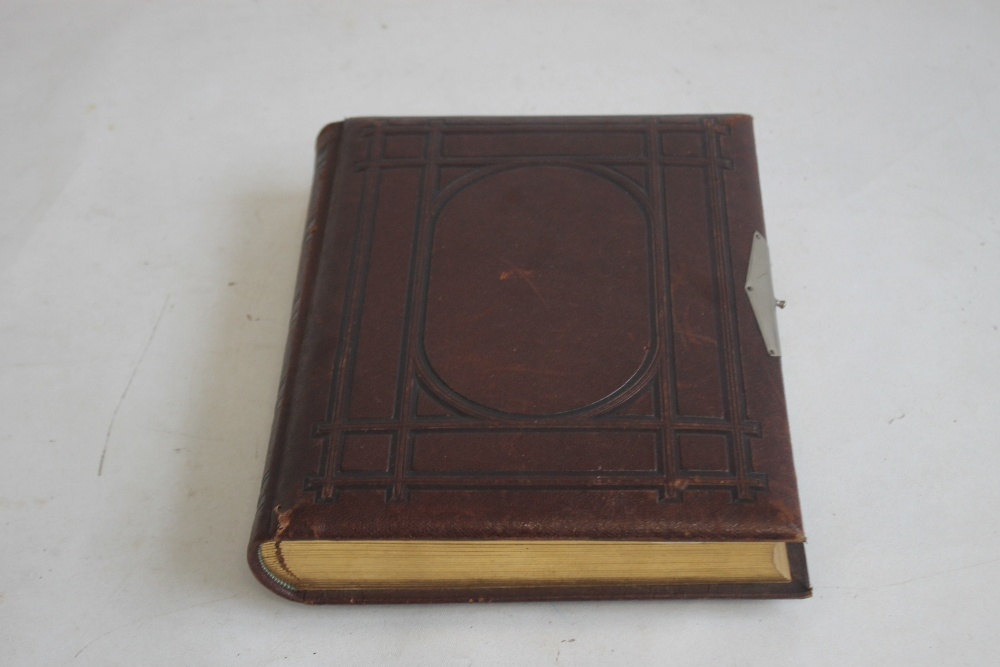 A VICTORIAN LEATHER BOUND PHOTOGRAPH ALBUM WITH CONTENTS, mainly portraits some decorated pages