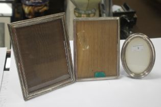 TWO HALLMARKED SILVER PICTURE FRAMES together with a white metal frame, the largest 23 x 17.5 cm