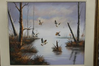 A GILT FRAMED OIL ON BOARD OF DUCKS IN FLIGHT OVER A RIVER, SIGNED BOND LOWER RIGHT, OVERALL