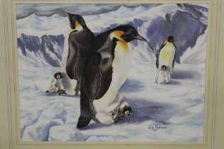 A FRAMED AND GLAZED WATERCOLOUR OF PENGUINS AND THEIR CHICKS SIGNED LIZ PODMORE 1987 LOWER RIGHT
