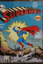 A FRAMED AND GLAZED REPRODUCTION ENAMEL PLAQUE OF A SUPERMAN COMIC COVER, OVERALL HEIGHT 58 CM