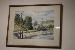 A FRAMED AND GLAZED WATERCOLOUR DEPICTING BOATS ON THE EDGE OF A VILLAGE SIGNED TO THE LOWER