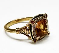 An 18ct gold ring with a central cushion cut citrine in a surround of bright brilliant-cut diamonds,