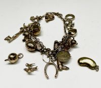 A 9ct gold charm bracelet with some 19 charms together with three loose charms. Total weight 24.6gm.