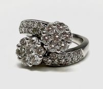 An 18ct white gold and diamond flowerhead crossover ring, 7.9g. Ring size O. Total diamond weight