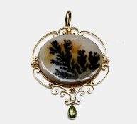 An Edwardian 15ct gold pendant set with a moss agate panel and with a peridot drop. 42mm wide 12.2gm