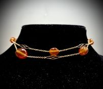 A delicate gold necklace with spaced pierced gold links and carnelian beads 14.9gm UK Postage: £17.0