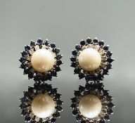 A pair of 18ct white gold earrings each with a pearl of 8.5mm within bands of diamonds and sapphires