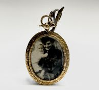 A Victorian high purity gold double-sided locket with chased decoration hanging from a swivel