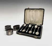 Three silver napkin rings together with a cased set of six silver coffee spoons 5.4oz. Condition: