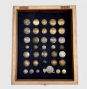 Livery Buttons (x36). Comprising a board mounted framed and glazed display of 36 brass and plated
