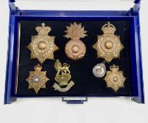 Royal Marines - 2. A blue plastic and glass display case containing 6 brass helmet badges, etc of