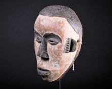 An Igbo mask, Nigeria, with short coiffure, highlighted in black against a white pigment ground,