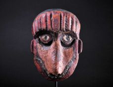 A carved and painted wood zoomorphic mask, Indonesia, painted predominantly in red and pink, with