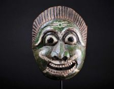 An Indonesian carved and painted wood mask, with linear coiffure, the face painted in white, green
