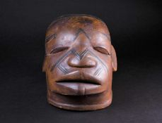 A Maconde Lipiko mask, Mozambique, carved with scarification marks, 24cm high, approximately 32cm