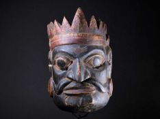An Indonesian carved and painted ceremonial male mask, in yellow, red, white and black pigment,
