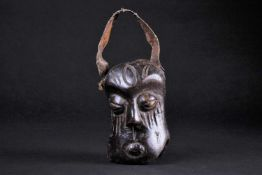 An African carved wood miniature mask/bell, the distorted face with coffee bean eyes and incised