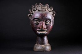 An Ejagham (Ekoi) leather bound carved wood headpiece, the head with numerous inset pegs, the maroon