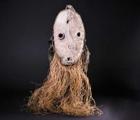 A Pende sickness mask, the remnants of feathers to the crest, the forehead with two inset rope twist