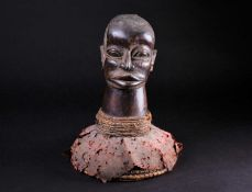 An Eket carved wood headdress, Nigeria, mounted on bound and woven straw covered in red material,