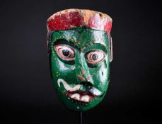 An Indonesian carved and painted wood sickness type mask, with distorted nose and mouth, pierced