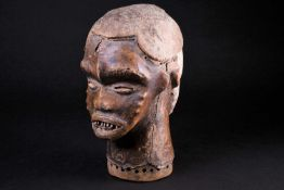 An Idoma Janus mask headdress, Nigeria, one face kaolin painted, the other covered in animal skin,