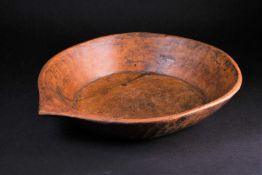 An Indian carved wood bowl, the rim terminating in a point, the exterior with adzed sloping sides, a