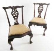 """A pair of George III carved and pieced mahogany """"Chippendale"""" style side chairs with bow-shaped"""