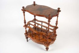 A Victorian figured walnut cartouch-topped three-tier table / Canterbury, with carved finials and