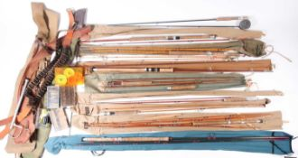A collection of early 20th century and later fishing rods, most in cloth bags, to include a