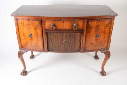 A George III style mahogany bow fronted kneehole and tambour sideboard, with ebony strung and