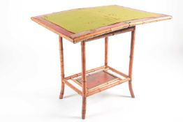 A 19th century bamboo and painted lacquer fold-over gaming table with under tier. Raised on slightly