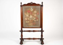 A Victorian mahogany and petit point firescreen, with shell and scroll decoration over turned