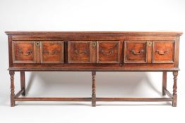 A Charles II style oak dresser base with three molded frieze drawers. Raised on turned supports