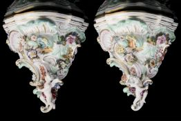 A pair of 19th c. Austrian, Vienna porcelain wall brackets with flower, scroll, and winged putto