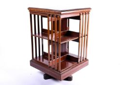 An Edwardian marquetry inlaid mahogany, revolving library bookcase in the manner of Edwards and