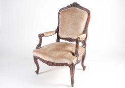 A French Louis XV style carved walnut fauteuil with stuff over back and seat. Raised on shaped