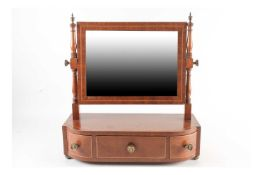 A George IV break bowfront, crossbanded and satinwood strung mahogany swing toilet mirror fitted