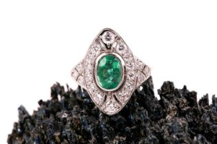 A platinum, diamond, and emerald ring, set with a mixed oval-cut emerald, within a navette-shaped