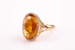 A 14ct yellow gold, diamond, and citrine cocktail ring, set with a large mixed oval-cut citrine