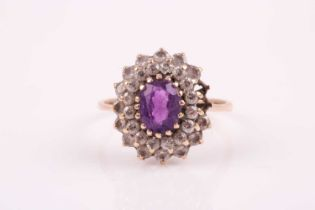 A 9ct yellow gold, amethyst, and white paste stone cluster ring, set with a mixed oval-cut