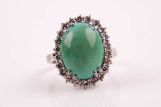 A diamond and turquoise cluster ring, set with an oval cabochon turquoise, within a border of