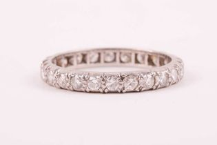 A diamond eternity ring; the mixed round brilliant-cut diamonds claw mounted within a slightly